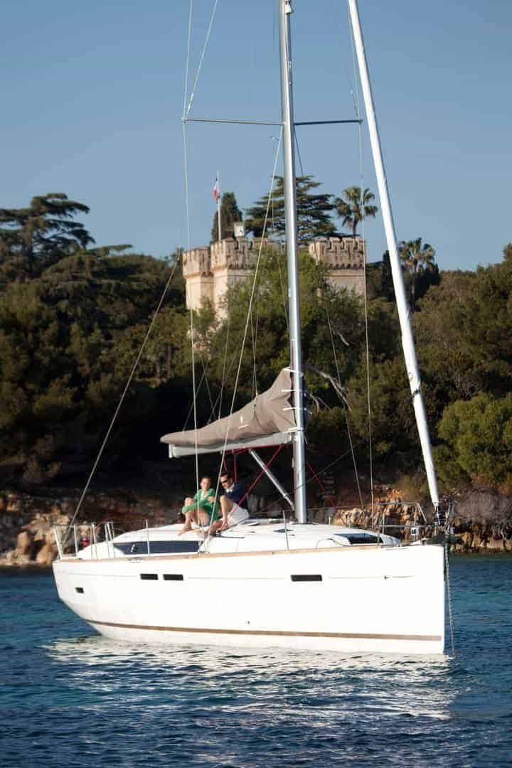 Floating Jeanneau Sun Odyssey 449 with a man and a woman relaxing on the deck with a castle in the background