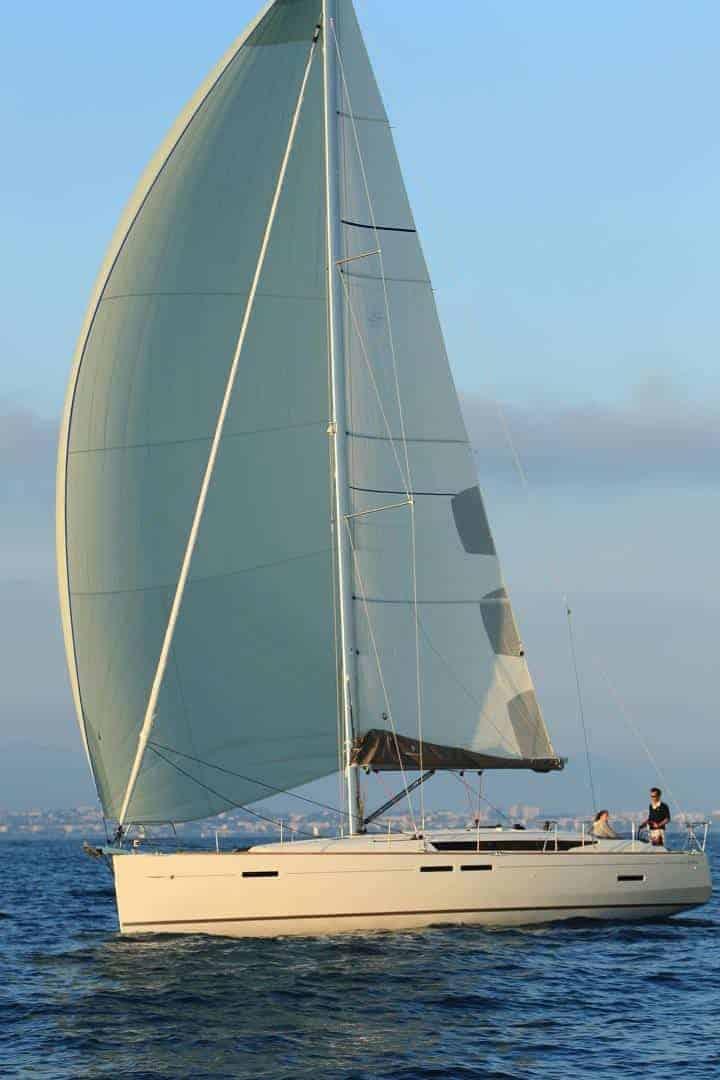 Jeanneau Sun Odyssey 449 sailing calmly ahead a stil and sunny day