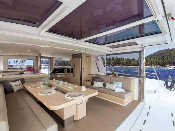 Set table on the deck of the spacious and gorgeous Bali 5.4 in a sunny and tropical landscape with palms on the beach