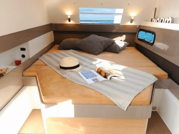 The bed in one of the cabins of a Bali 4.3 with a towel and hat on it