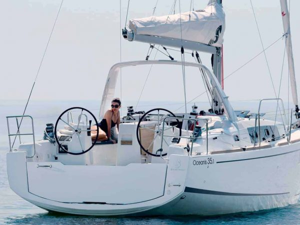 Beneteau Oceanis 35.1 cruising ahead on a sunny day on still water while a lady relaxes on deck