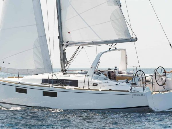 Beneteau Oceanis 35.1 sailing on still water with a woman at one of the steering wheel