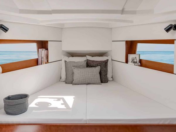 Really cozy looking bed in the Beneteau Oceanis 35.1 with white quilt and walls with nice wooden details and windows on the sides of the cabin
