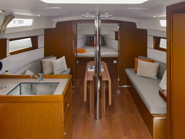 Saloon of the elegant Beneteau Oceanis 35.1 with the mast in the center and the cabin door open in the background so that the bed gets exposed