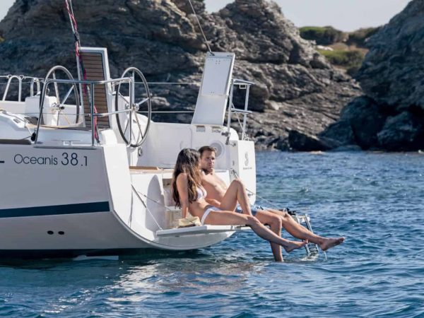 Couple relaxing and sun bathing togheter at the transom hatch