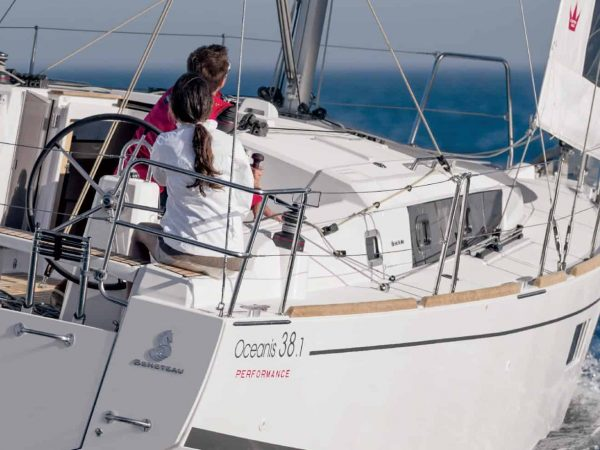 The Beneteau 38.1 in action, couple sailing through the calm waves