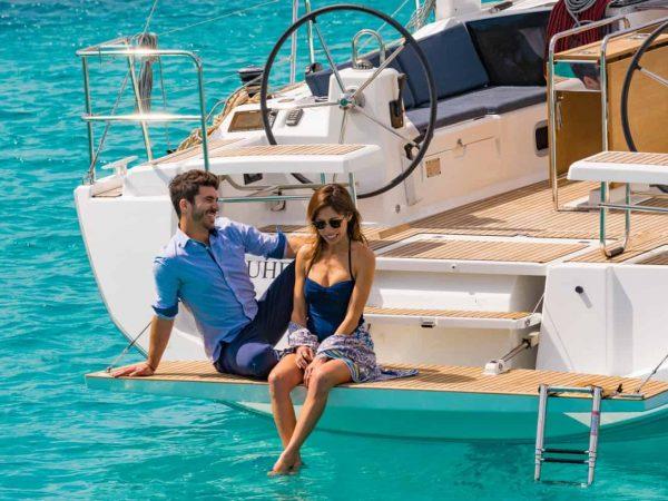 Couple enjoying eachother on transom of the Benteteau Oceanis 44.1