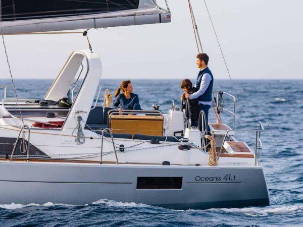 Family enjoying the Benteteau Oceanis 44.1 while sailing through the crashin waves