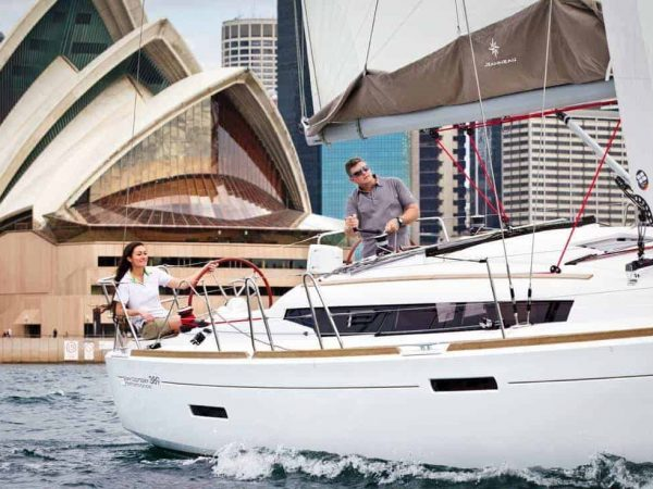 Jeanneau Sun Odyssey 389 sailing infront of Opera Australia with a man and a woman on deck