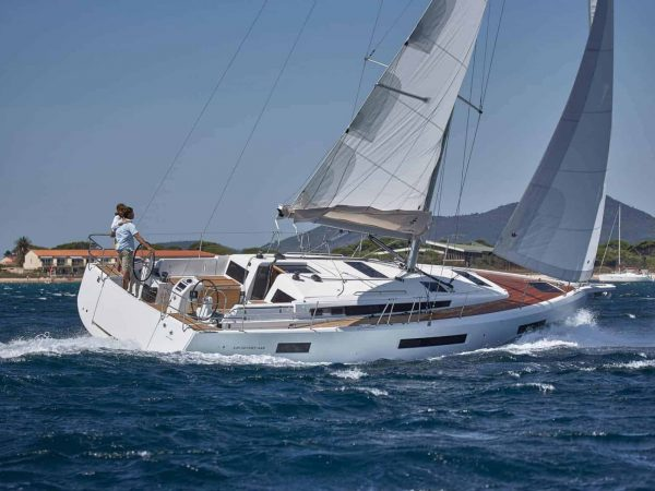 Jeanneau Sun Odyssey 440 in action with wind in its sails and the captain at the steering wheel