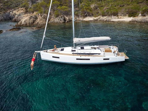 Anchored Jeanneau Sun Odyssey 440 close to the coastline and a man dives into the sea from deck