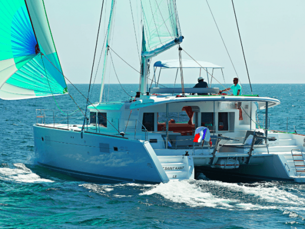 Lagoon 450 F in action with wind in its sail with two guys at the flybridge