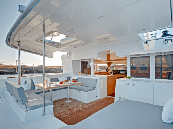 The spacious deck of the Lagoon 450 F with nice lounge sofas and a table with water bottles and plates