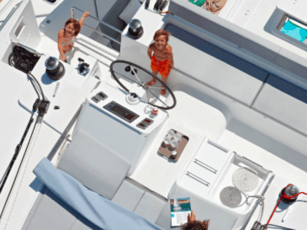 Aerial view down to the flybridge of the Lagoon 450 F with a boy at the steering wheel, a girl next to him and a woman lying on the lounger reading a magazine