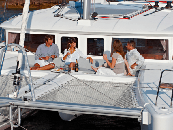 Two men and two woman having a snack and champagne on the deck of the docked Lagoon 450 F