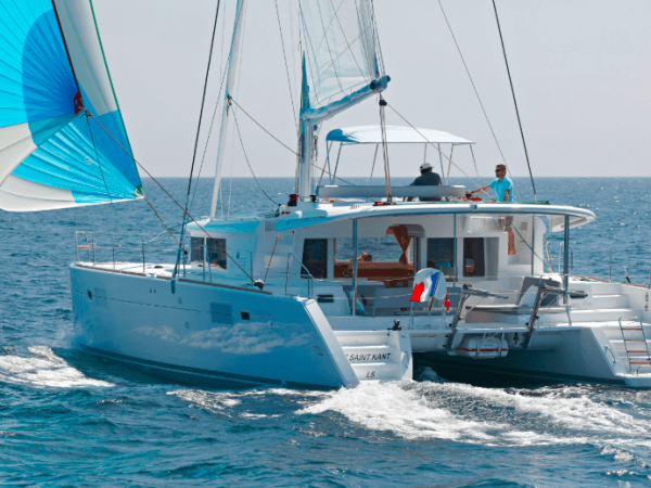 Lagoon 450 F in actin with wind in its sail with two guys at the flybridge