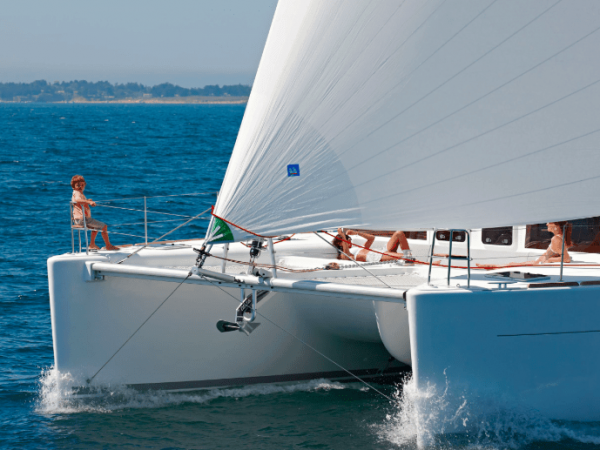 A boy and two woman relaxes on the front deck of the Lagoon 450 F while its sailing