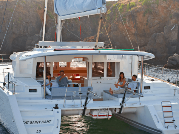 Two men and two woman chilling on the deck of the yacht Lagoon 450, docked next to some cliffs