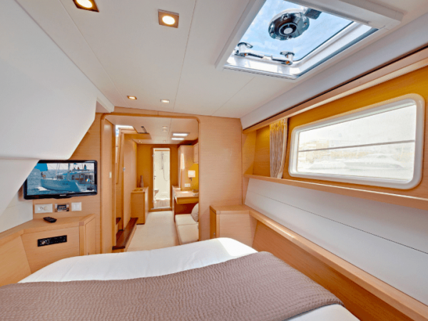 View from the bed of a Lagoon 450 showing the television, windows on the wall and roof and the hallway