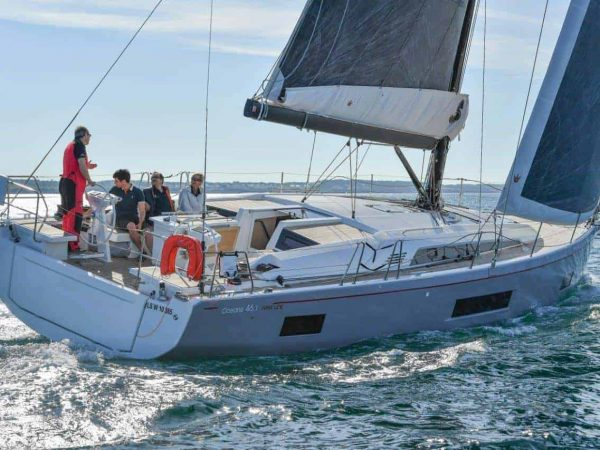 People hanging out on the cockpit of Beneteau Oceanis 46.1 while it sails ahead during a sunny day