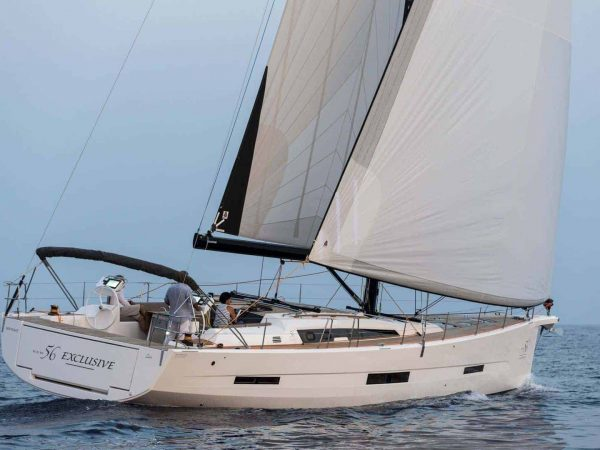 Family sailing the Dufour Exclusive 56 through the waves with wind in sail